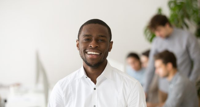 Happy african american professional smiling looking at camera with colleagues at background, friendly black business coach, successful intern, team leader member posing in office, head shot portrait